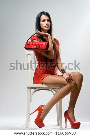 Moody shot of stylish brunette fashion beauty on white chair. - stock photo