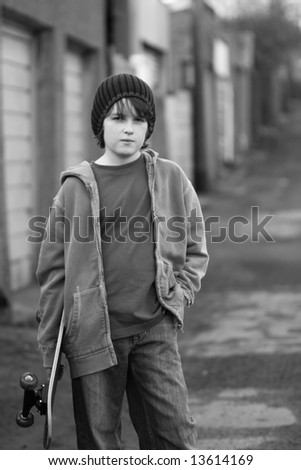 Moody skateboarder in an alleyway, black and white - stock photo