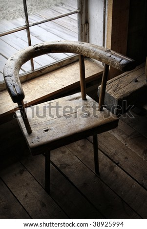 Moody, still life scene of an authentic 19th century hand-made wooden chair in the ambient light of a window. - stock photo