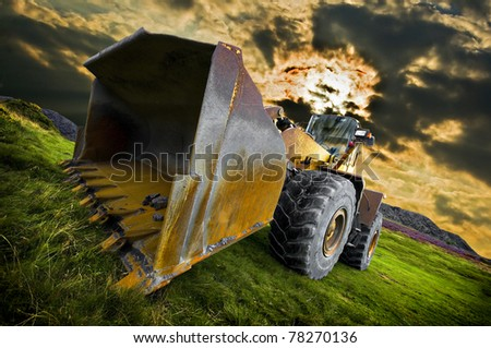 moody threatening image of a heavy wheel or front end loader with a dramatic sky beyond. - stock photo