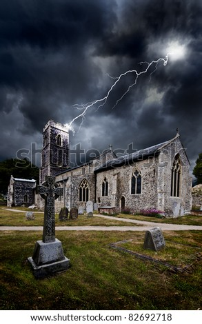 moody threatening image of a thirteenth century english church being struck by a lightning bolt during a dramatic and threatening electrical storm - stock photo