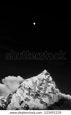 Moon and Nuptse (7864 m) at sunset (black and white) - Everest region, Nepal, Himalayas - stock photo