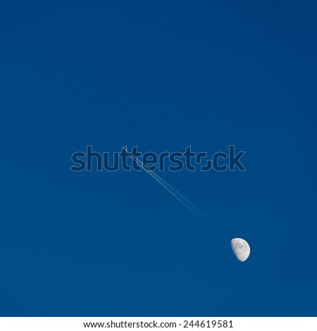 Moon and passenger airplane in blue sky, large trail of the plane - stock photo