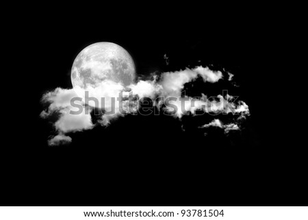 Moon between the clouds in dark night, a dark night brings a bright, amber moon alive with puffy hazy clouds. - stock photo