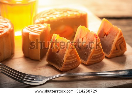 Moon cake, Chinese mid autumn festival dessert on wood board with dramatic morning scene - stock photo