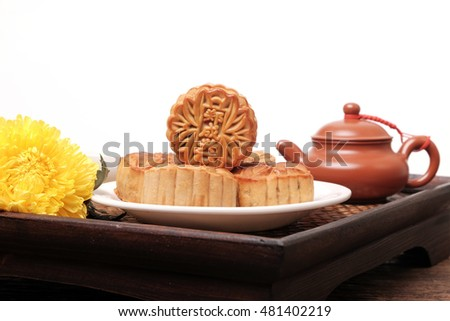Moon cakes and tea on wooden tray with white space for text, background for the Chinese Mid-Autumn festival.