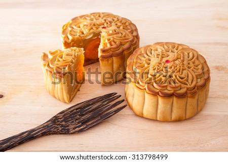 Moon cakes for the chinese Mid-Autumn festival with one cut up to show egg yolk and wooden fork, on wooden background - stock photo