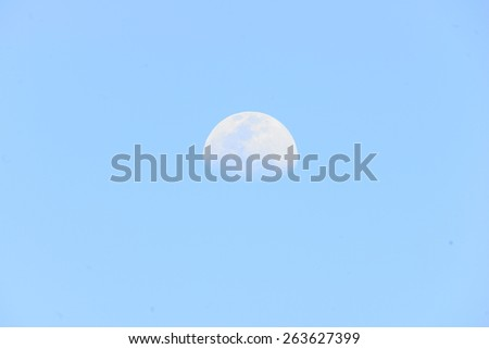 Moon  closeup showing the details of the lunar surface on blue sky - stock photo