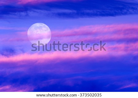 Moon clouds is a soft beautiful cloudscape over a blue sky with a silhouetted flock of birds flying by as a bright full moon rises in the evening sky. - stock photo