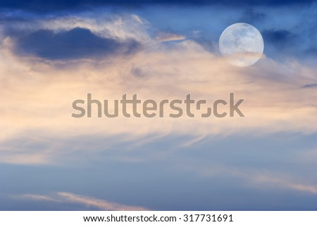 Moon clouds is a soft colorful scenic cloudscape against a blue sky with the full moon rising in as it sits behind some wispy colorful clouds. - stock photo