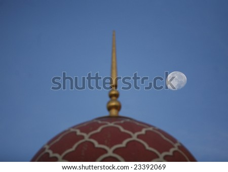Moon hangs over the dome of Malaysia's landmark Putra Mosque. - stock photo