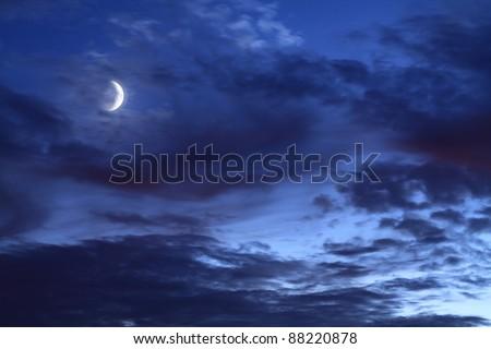 Moon in dark blue cloudy sky - stock photo