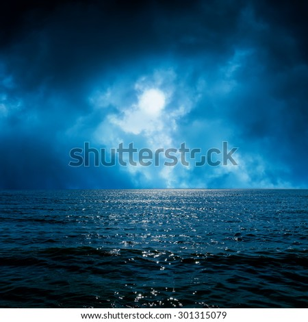 moon light in dramatic sky over dark sea - stock photo