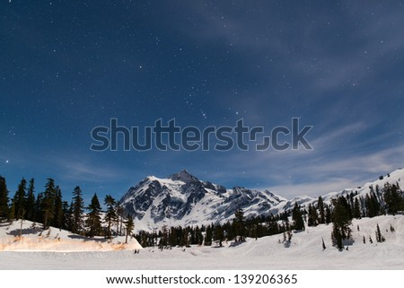 Moon light lights up the Mount Baker and Picture Lake which is covered by thick snow. But still see the stars in the sky. - stock photo