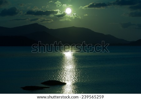 moon lighting at the sea with mountains silhouettes - stock photo