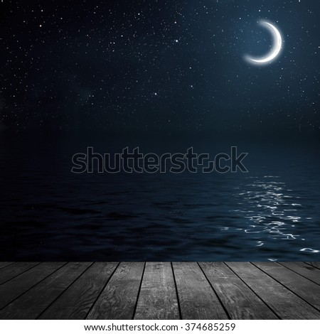 moon on a background star sky reflected in the sea. wood - stock photo