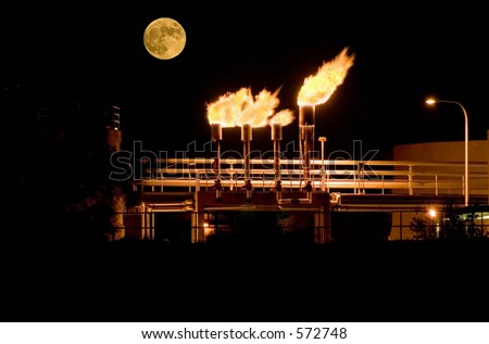 Moon over methane gas burners at waste water treatment plant - stock photo