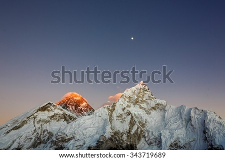 Moon over Mount Everest and Nuptse at sunset (view from Kala Patthar) - Nepal, Himalayas - stock photo