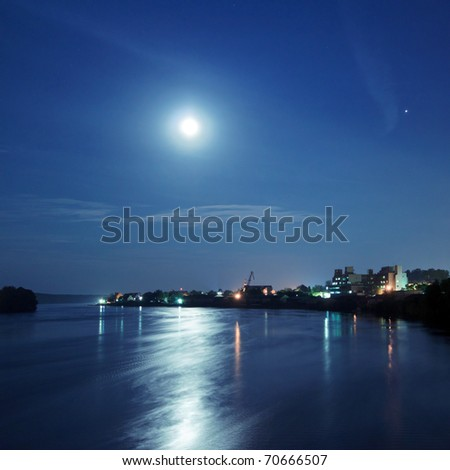 Moon over the river by the town - stock photo