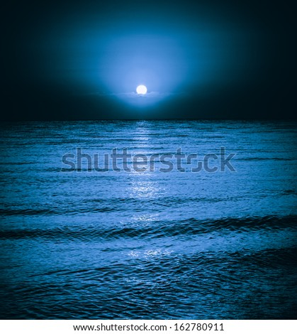 Moon reflecting in a lake sea ocean waves. Moonlight night background - stock photo