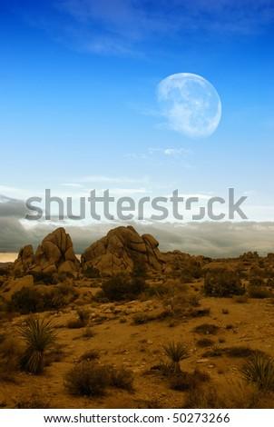 Moon rising over desert landscape in Joshua Tree national park. - stock photo