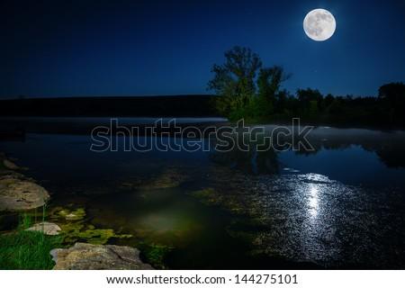 Moon rising over lake - stock photo
