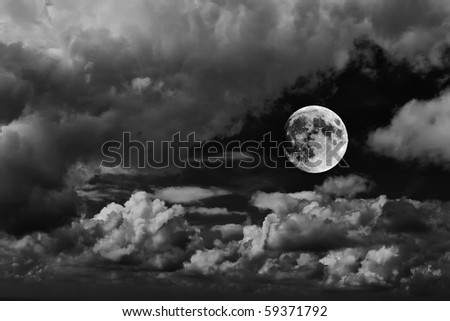 moon with dark clouds in black and white - stock photo