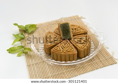 Mooncake, a Chinese bakery product traditionally to be eaten during the Mid Autumn Festival. This is of green tea paste fillings and from triangle shaped moulding, placed in a clear plastic plate.  - stock photo