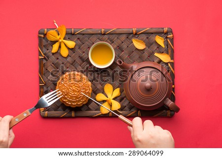 Mooncake and tea,Chinese mid autumn festival food. hand with a knife cutting the cake. angle view from above - stock photo