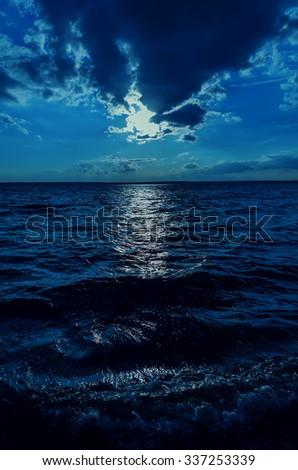 moonlight in sky over dark water - stock photo