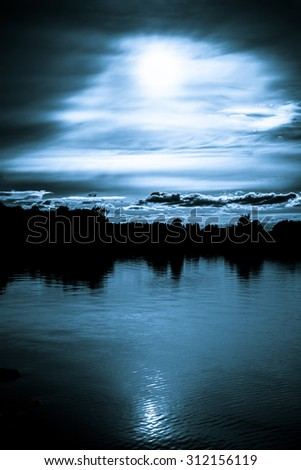 Moonlight in the clouds over a lake with forest in the background