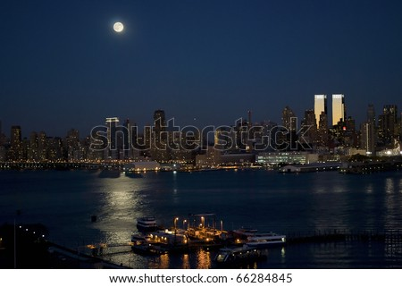 Moonlight on the Hudson River with a full moon over the New York City skyline. - stock photo