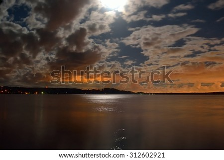 Moonlit night and clouds on night sky in the lake. - stock photo