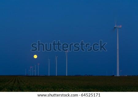 Moonrise over a wind farm - stock photo