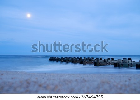 Moonrise over an Atlantic Ocean Beach full of sand and crushed shells - stock photo