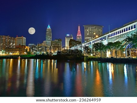Moonrise over Cleveland Ohio with the Veterans Memorial Bridge angling in and beautiful reflections on the Cuyahoga river in the foreground. - stock photo