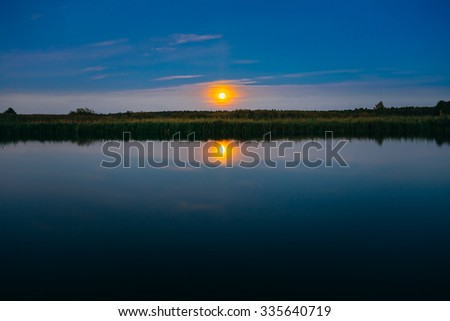Moonrise over river lake pond in summer evening. Calm Water, Forest On Other Side. Landscape. Nature Background - stock photo