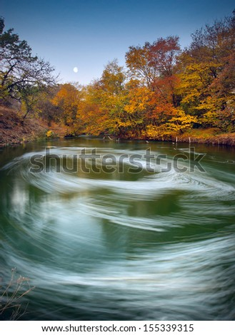 Moonrise over the autumn river with beautiful whirlpool - stock photo