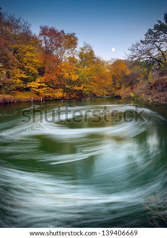 Moonrise over the Autumn river with whirlpool - stock photo
