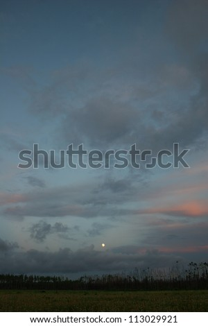 moonrise through clouds over field - stock photo