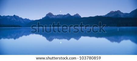 Moonset at sunrise over Redfish Lake and Sawtooth Mountains, Idaho - stock photo