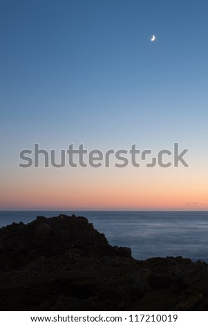 Moonset over rocky coast. A sharp silhouette of rocks can be seen in the foreground and a beautiful color gradient from orange to blue is visible in the background. - stock photo