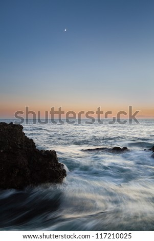 Moonset over rocky ocean. A sharp silhouette of rocks can be seen in the foreground and a beautiful color gradient from orange to blue is visible in the background. - stock photo
