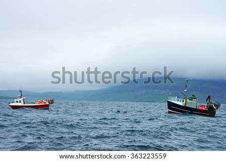 Moored boats on Loch Scavaig sitting out an incoming storm with low cloud and sea mist covering the distant Cuillin Hills in Summer, Elgol, The Isle of Skye, Scotland - stock photo