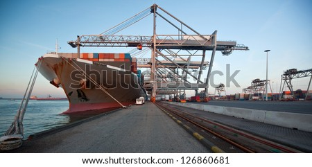 Moored container ship and gantry cranes - stock photo