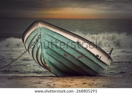 Moored green row boat in rough sea at sunset, vintage style - stock photo