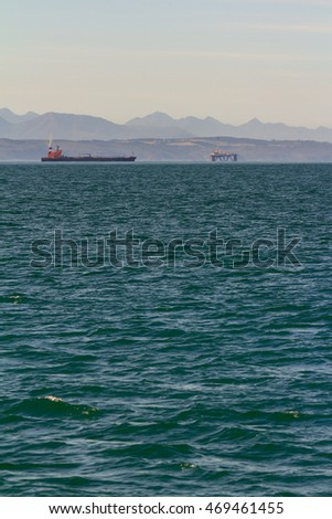 moored oil tanker with an oil rig in the background and a distant heat haze
