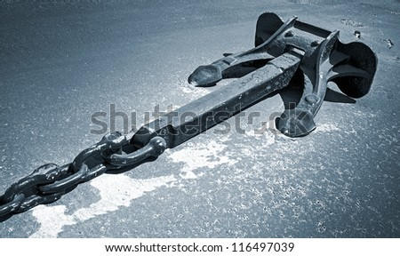 Mooring anchor with chain on dry ground. Monochrome photo - stock photo
