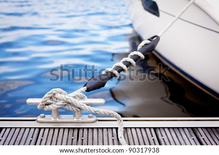 Mooring at a pier/ A white yacht moored with a line tied around a metal fixing on the quayside. - stock photo