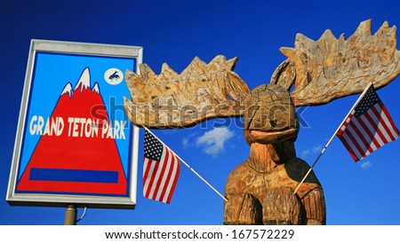 Moose statue with USA flags at Grand Teton park sign in northwestern Wyoming, USA - stock photo
